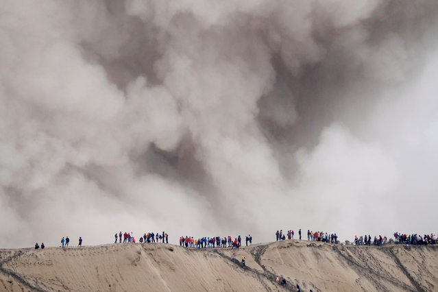 Mount Bromo spews ash as Hindu villagers and visitors stand on the edge of the volcanic crater ahead of Kasada ceremony, when villagers and worshippers throw offerings livestock and other crops into the volcanic crater of Mount Bromo, in Probolinggo, Indonesia, July 20, 2016. (Photo by Reuters/Beawiharta)