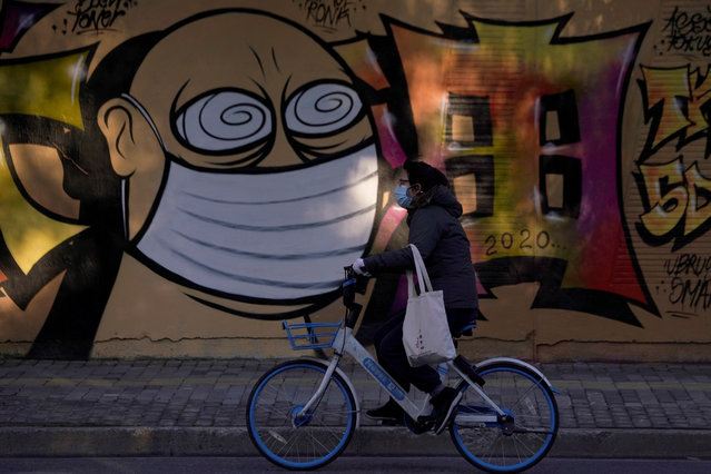 A woman wearing a protective mask cycles past graffiti-painted wall at a construction site in Shanghai, China, as the country is hit by coronavirus outbreak, February 17, 2020. (Photo by Aly Song/Reuters)