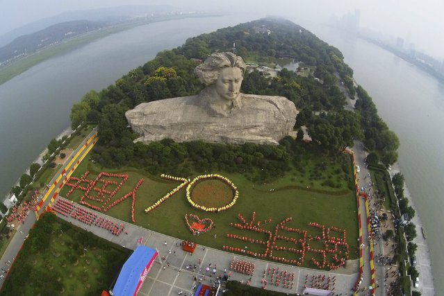 """Participants form the figure """"70"""" and the Chinese characters """"The Chinese people shall strive to become stronger"""" in front of a statue of China's late Chairman Mao Zedong in his youth, during an event to celebrate the 70th anniversary of the end of World War Two in Changsha, Hunan province, China, August 30, 2015. (Photo by Reuters/Stringer)"""