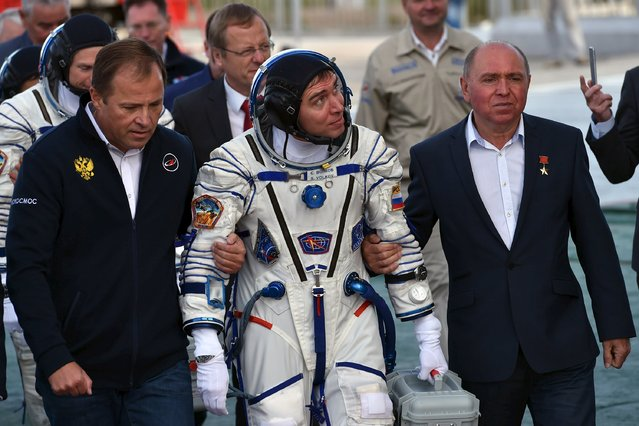 Russian cosmonaut Sergei Volkov (C), his father Soviet cosmonaut Aleksander Volkov (R) and Roskosmos agency's head Igor Komarov go to board the Soyuz TMA-18M spacecraft at the Russian-leased Baikonur cosmodrome early September 2, 2015. (Photo by Kirill Kudryavtsev/Reuters)