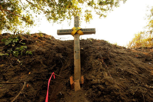 A cross is seen at the site where bulldozer operator Robert Reagan of Fresno County was killed in a rollover on July 26, 2016 while fighting the Soberanes Fire, in the Palo Colorado area north of Big Sur, California, July 31, 2016. (Photo by Michael Fiala/Reuters)