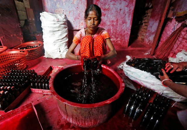 A worker fills bottles with Alta, a red dye which Hindu women apply with cotton on the border of their feet during marriages and religious festivals, at a workshop in Kolkata, India August 2, 2016. (Photo by Rupak De Chowdhuri/Reuters)