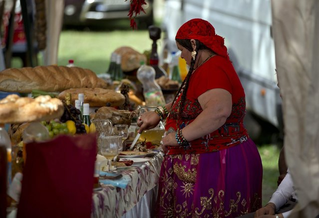 A Roma woman cuts food as the Roma community celebrates the Birth of the Virgin Mary in Costesti, Romania, Monday, September 8, 2014. (Photo by Vadim Ghirda/AP Photo)