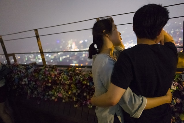 A couple have conversation while watching the night view of Seoul from the observation deck on the top of Namsan mountain on July 30, 2015 in Seoul, South Korea. (Photo by Shin Woong-jae/The Washington Post)
