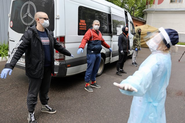 A group of conscripts, wearing face masks to protect against coronavirus, stand during a medical checkup at a military conscription office in Moscow, Russia, Friday, May 22, 2020. The Russian military has launched a regular draft despite the coronavirus pandemic. (Photo by Kirill Zykov, Moscow News Agency photo via AP Photo)