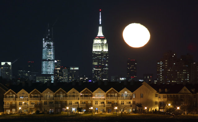 The moon rises behind the Empire State Building in New York City and homes in Jersey City, New Jersey on January 12, 2020 as seen from Newark, New Jersey. (Photo by Gary Hershorn/Getty Images)