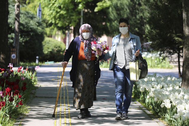 An elderly woman wearing a face mask to protect against coronavirus, holds flowers she have received on the Mother's Day in a public garden during a two-day curfew declared by the government in an attempt to control the spread of coronavirus, in Ankara, Turkey, Sunday, May 10, 2020. Only senior people over 65 have been allowed to go out for four hours on Sunday. (Photo by Burhan Ozbilici/AP Photo)