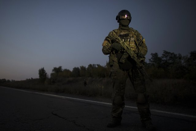 A Ukrainian soldier stands guard on a road during a prisoners-of-war (POWs) exchange, north of Donetsk, eastern Ukraine, September 28, 2014. (Photo by Marko Djurica/Reuters)