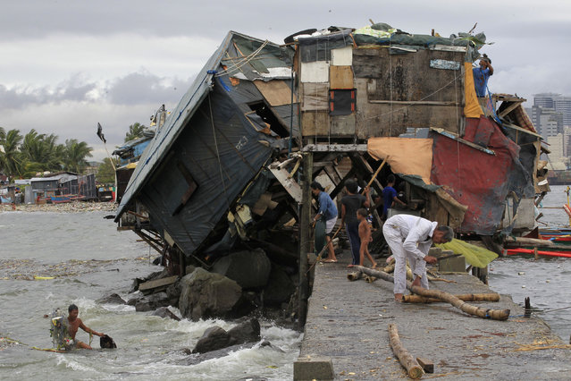 People work around a damaged house along the coastal area after strong winds brought by Typhoon Rammasun battered the Baseco compound, metro Manila July 17, 2014. (Photo by Romeo Ranoco/Reuters)