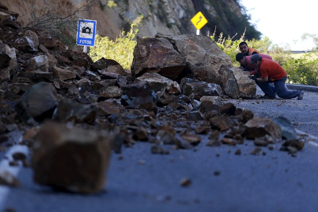 Workers try to remove a rock on the road to Illapel town after an earthquake hit areas of central Chile,  September 17, 2015. (Photo by Ivan Alvarado/Reuters)