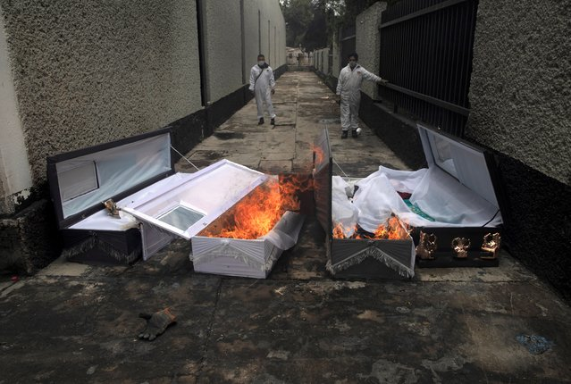 Crematorium workers burn the coffins of COVID-19 victims after they have been cremated at the San Nicolas Tolentino cemetery in the Iztapalapa neighborhood of Mexico City, Wednesday, June 24, 2020. (Photo by Marco Ugarte/AP Photo)