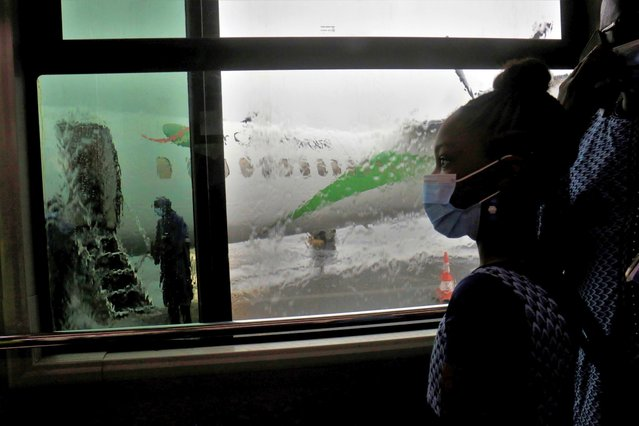 A girl looks at a plane out of a bus window, during the first day of resumed Air Cote d'Ivoire internal flights amid the coronavirus disease (COVID-19) outbreak, at Felix Houphouet Boigny International airport in Abidjan, Cote d'Ivoire on June 26, 2020. (Photo by Thierry Gouegnon/Reuters)
