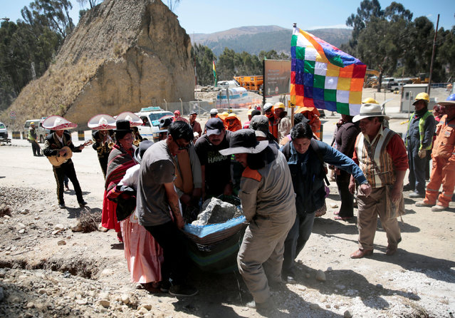 """Aymara people carry a stone which bears an impression that locals refer to as """"Devil face"""", as a shrine frequented by indigenous witch doctors is removed to expand a main highway between La Paz and El Alto, Bolivia, August 24, 2016. (Photo by David Mercado/Reuters)"""