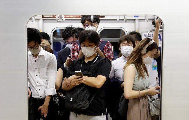 Passengers wearing protective masks amid the coronavirus disease (COVID-19) outbreak, ride a subway train in Tokyo, Japan, July 3, 2020. (Photo by Kim Kyung-Hoon/Reuters)