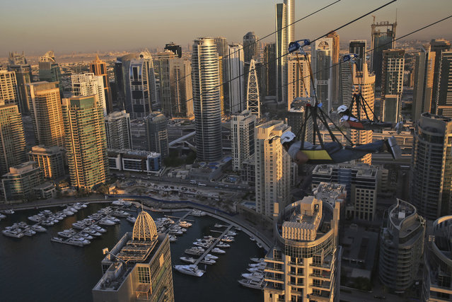 Two people ride the world's longest urban zip line with a speed of up to 80 kilometers per hour on a one kilometer run from 170 meter to ground level, at the Marina district of Dubai, United Arab Emirates, Tuesday, December 5, 2017. (Photo by Kamran Jebreili/AP Photo)