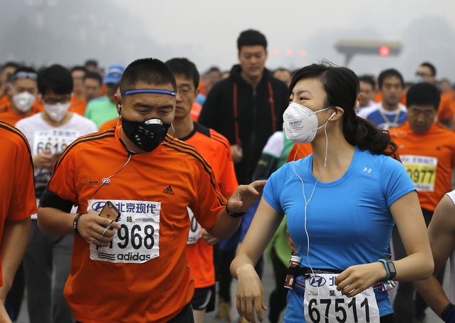 Runners wearing masks to protect themselves from pollutants jog past Chang'an Avenue near Tiananmen Square shrouded in haze while taking part in the 2014 Beijing International Marathon in Beijing, China Sunday, October 19, 2014. (Photo by Andy Wong/AP Photo)