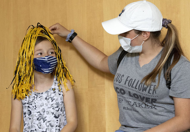 University of Idaho freshman Layla Houston of Spokane, Wash., right uses a pom-pom to give her sister, Lillian Houston, hair style in school colors during UIdaho Bound, on Friday, July 17, 2020, in Moscow, Idaho. More than 200 University of Idaho freshmen and their families participated in the event. The sisters were wearing face masks to help prevent the spread of the coronavirus. (Photo by Geoff Crimmins/The Moscow-Pullman Daily News via AP Photo)