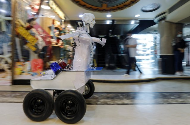 The remote-controlled robot that was built by Egyptian mechanical engineer, Mahmoud El komy, 26, moves in a mall to test people for the coronavirus by running PCR tests and limiting exposure to suspected cases in Cairo, Egypt on June 12, 2020. (Photo by Mohamed Abd El Ghany/Reuters)