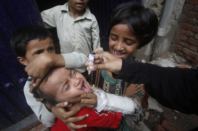 A health worker gives a polio vaccine to a child in Lahore, Pakistan, Tuesday, July 21, 2020. Pakistan resumed vaccinations against polio, months after the drive against this crippling children's disease was halted because the novel coronavirus had overwhelmed the country's health system. (Photo by K.M. Chaudary/AP Photo)