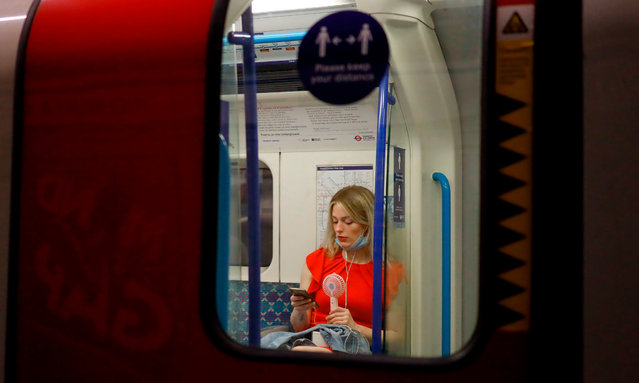 A woman fans herself with an electric fan as she looks at her smartphone on the tube in central London as the temperature rises in the capital on July 31, 2020. (Photo by Tolga Akmen/AFP Photo)