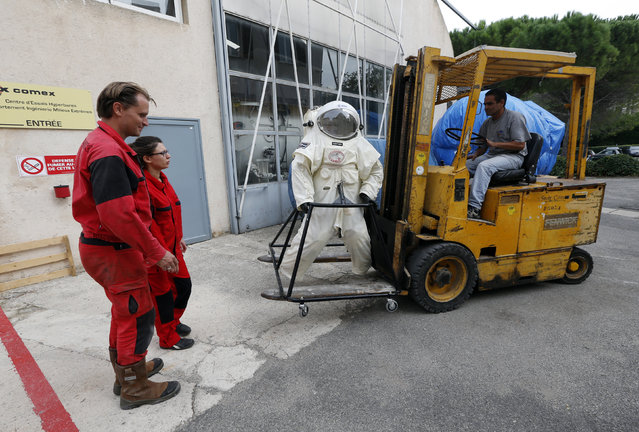 Comex Space division manager Peter Weiss (L) and Comex project engineer Virginie Taillebot (2ndL) move the Gandolfi space suit before a training session in Marseille October 21, 2014. (Photo by Jean-Paul Pelissier/Reuters)