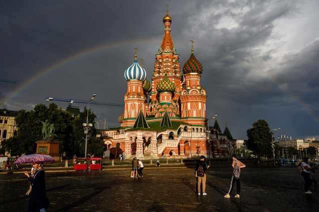People walk in front of St. Basil Cathedral lit by the sun with a rainbow in the background on Red Square in Moscow, on July 20, 2020. (Photo by Dimitar Dilkoff/AFP Photo)