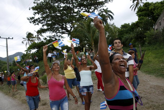 People cheer and wave flags as Pope Francis drives past in El Cobre, Cuba, September 21, 2015.. (Photo by Carlos Garcia Rawlins/Reuters)