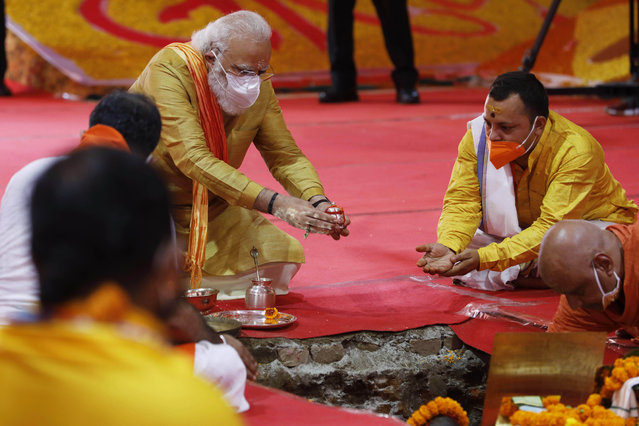 Indian Prime Minister Narendra Modi performs the groundbreaking ceremony of a temple dedicated to the Hindu god Ram, in Ayodhya, India, Wednesday, August 5, 2020. The coronavirus is restricting a large crowd, but Hindus were joyful before Prime Minister Narendra Modi breaks ground Wednesday on a long-awaited temple of their most revered god Ram at the site of a demolished 16th century mosque in northern India. (Photo by Rajesh Kumar Singh/AP Photo)