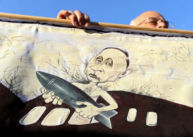 An opposition supporter holds a placard depicting President of Russia Vladimir Putin during an opposition rally against the deployment of Russian military base in Belarus in Minsk, Belarus, 04 October 2015. Presidential elections in Belarus will be held on 11 October 2015. Presidential elections in Belarus will be held on 11 October 2015. (Photo by Tatyana Zenkovich/EPA)