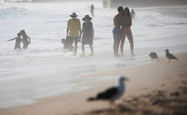 Couples enjoy the weather on the beach during a heat wave as the outbreak of the coronavirus disease (COVID-19) continues, in Pacific Palisades, California, U.S., August 19, 2020. (Photo by Mario Anzuoni/Reuters)
