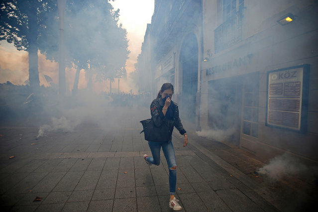 A woman runs away from tear gas during clashes with French riot police at a march in Nantes, western France, to demonstrate against the new French labour law, September 15, 2016. (Photo by Stephane Mahe/Reuters)