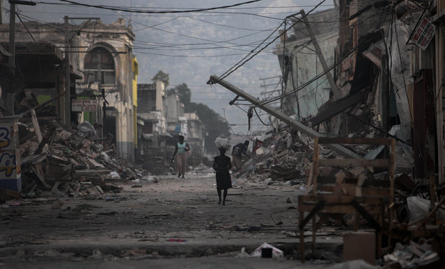 A woman walks down a devastated street in Port-au-Prince, Wednesday, January 20, 2010.  A powerful 7.0-magnitude earthquake struck Haiti last week. (Photo by Gregory Bull/AP Photo)