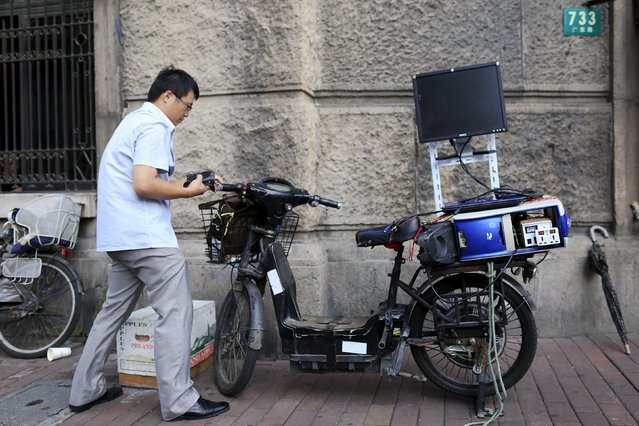 """Yue Banghai moves his electric bike during a """"street stock salon"""" in central Shanghai, China, September 5, 2015. Yue is a businessman who's been selling futures and stocks analysis software for five years. Every weekend, when is not raining, Yue rides electronic bike to the salon where he offers his software using a computer attached to the back seat of his bike.  (Photo by Aly Song/Reuters)"""