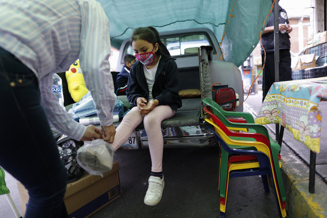 """Neighborhood volunteer Rebeca Rodriguez ties plastic bags over the shoes of Paulina Mariano Ortiz who arrives for a lesson in the bed of a pick-up truck repurposed as an educational space on the southern edge of Mexico City, Friday, September 4, 2020. Concerned about the educational difficulties facing school-age children during the coronavirus pandemic, the couple who runs """"Tortillerias La Abuela,"""" or Grandma's Tortilla Shop, adapted several spaces outside their shop to provide instruction and digital access to local children who don't have internet or TV service at home, a project that has attracted donations and a waiting list of students. (Photo by Rebecca Blackwell/AP Photo)"""