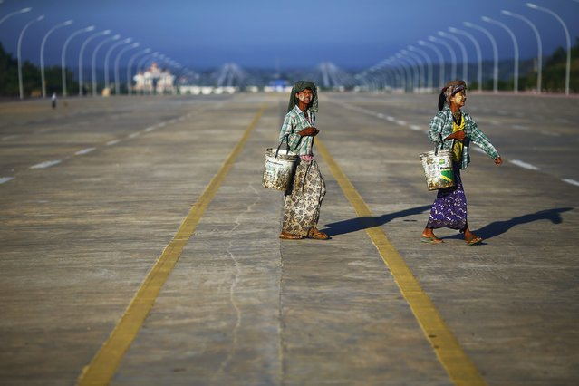 """Construction workers carry buckets on an empty 20 lane road leading to the country's parliament building in Naypyitaw November 11, 2014. Yangon lost its status as Myanmar's capital in 2005, after the former military junta carved a new seat of government from a parched wilderness some 380 km (236 miles) to the north and called it Naypyitaw (""""Abode of Kings""""). (Photo by Damir Sagolj/Reuters)"""