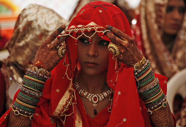 An Indian bride adjusts her veil during a mass marriage ceremony in Ahmadabad, India, Sunday, October 11, 2015. Sixty five Muslim couples tied the knot in a single ceremony organized by a social organization. (Photo by Ajit Solanki/AP Photo)