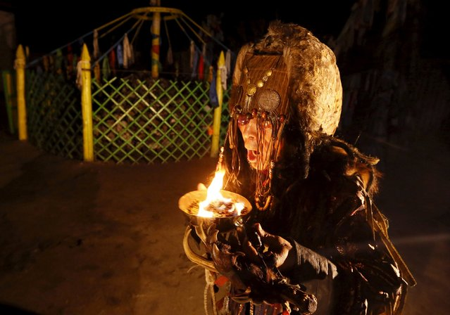 A shaman, representing the so-called Adyg Eeren (Bear Spirit) society, together with its other members, participates in the so-called Kamlanie night ritual upon the request of customers, including local residents and foreigners, in the town of Kyzyl, the administrative centre of Tuva region, Southern Siberia, Russia, October 9, 2015. (Photo by Ilya Naymushin/Reuters)