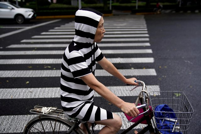 A woman rides a bicycle on a street, following the coronavirus disease (COVID-19) outbreak in Shanghai, China on September 17, 2020. (Photo by Aly Song/Reuters)