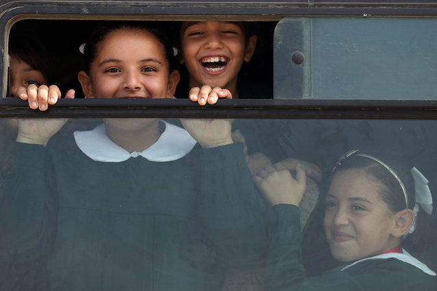 Palestinian school girls smile to the camera as they come back home in their school bus on September 22, 2016 in Gaza City. (Photo by Mohammed Abed/AFP Photo)