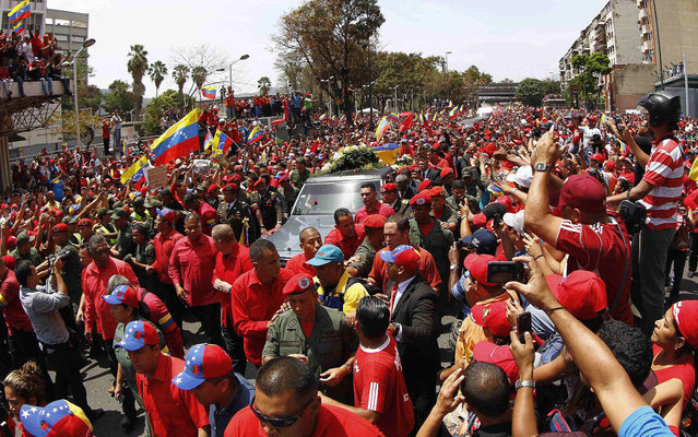 Crowd accompanies the procession carrying the coffin of Chávez in Caracas. (Photo by Carlos Garcia Rawlins/Reuters)