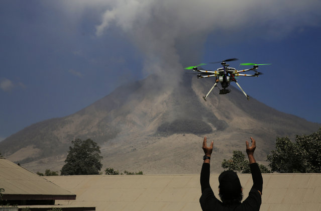 An official of the Center for Research and Technology Volcanoes Development releases a drone quadcopter to monitor activity from the Mount Sinabung volcano at Sibintun village in Karo district, North Sumatra province, Indonesia, February 4, 2014. (Photo by Reuters/Beawiharta)