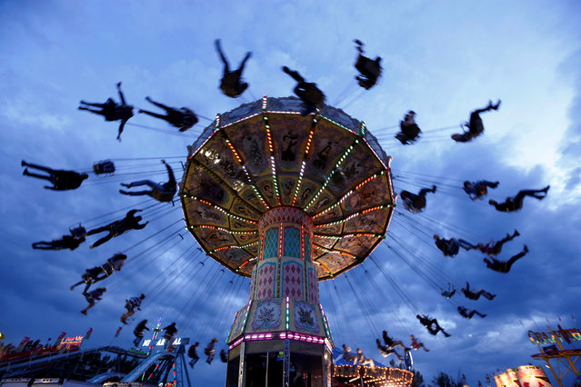 People swing on a ride in the midway during the Calgary Stampede in Calgary, Alberta, Canada July 14, 2016. (Photo by Todd Korol/Reuters)