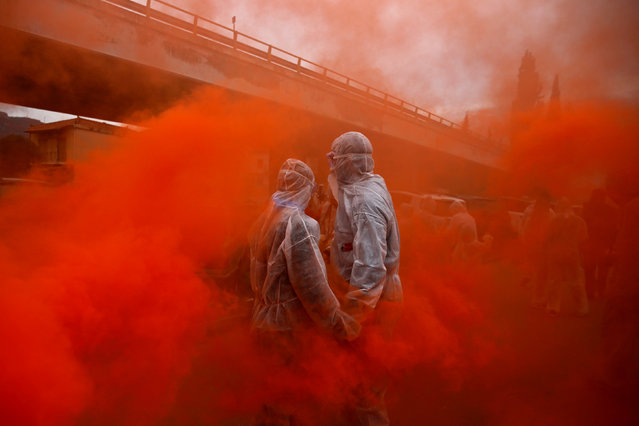 "Two revellers are seen amid flare smoke as they celebrate ""Ash Monday"" by participating in a colourful ""flour war"", a traditional festivity marking the end of the carnival season and the start of the 40-day Lent period until the Orthodox Easter, in the port town of Galaxidi, Greece February 19, 2018. (Photo by Alkis Konstantinidis/Reuters)"