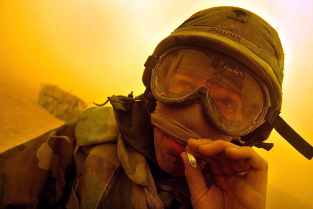 A U.S. Army combat engineer enjoys a cigarette as he relaxes between the cities of Najaf and Karbala as another sandstorm turned the daylight orange, on March 26, 2003. (Photo by Kai Pfaffenbach/Reuters/The Atlantic)