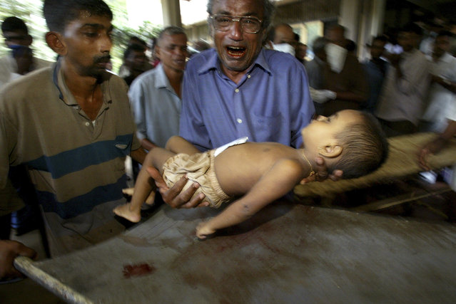 A Sri Lankan man cries as he carries the body of a young relative to a hospital in Karapitiya outside Galle in this December 27, 2004 file photo. (Photo by Thomas White/Reuters)