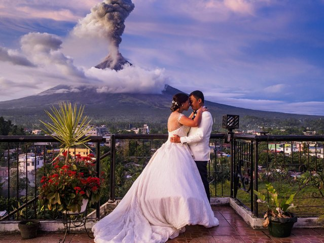 Arlo Dela Cruz and Maica Nicerio-Dela Cruz on their wedding day with the Mayon volcano erupting in the background, in Daraga, Albay, Philippines on January 25, 2018. They were married earlier in the afternoon at Our Lady of the Gate Parish. After their wedding they walked out to Red Labuyo restaurant and the volcano started its eruption. The Mayon volcano continued to erupt Thursday. The airport in Legazpi is closed until at least 31 January 2018. (Photo by ZUMA Press/Alamy Stock Photo)