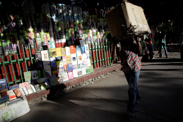 A man carrrying a box walks next to electoral posters plastered on a wall behind books on display for sale in a street of Port-au-Prince, Haiti, September 21, 2016. (Photo by Andres Martinez Casares/Reuters)