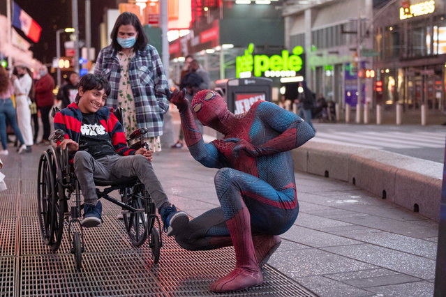 Junaid watches as Andreas Alfaro, dressed in a Spider- Man costume, makes the Spider-Man web shooting hand gesture in Times Square during the Coronavirus pandemic on October 19, 2020 in New York City. (Photo by Alexi Rosenfeld/Getty Images)