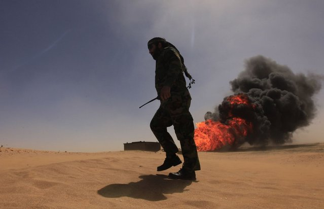 A security officer walks past a gas pipeline after an explosion, 18 km (11 miles) south of the city of Ajdabiyah April 3, 2013. Libya is investigating the cause of the explosion late on Tuesday on oil and condensate pipelines to the eastern port of Zueitina, the National Oil Corporation (NOC) said. It quoted acting NOC Chairman Abdulkasir Shengir as saying there were no casualties. (Photo by Esam Al-Fetori/Reuters)