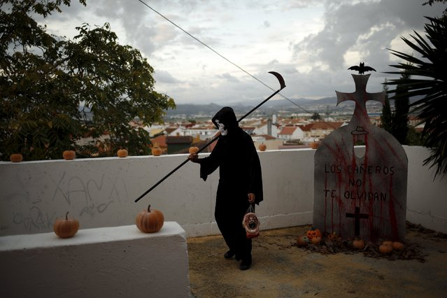 """A man dressed as the Grim Reaper walks as he takes part in the second edition of """"Noche del Terror"""" (Horror night) during Halloween celebrations in the neighborhood of Churriana, near Malaga, southern Spain, October 31, 2015. (Photo by Jon Nazca/Reuters)"""
